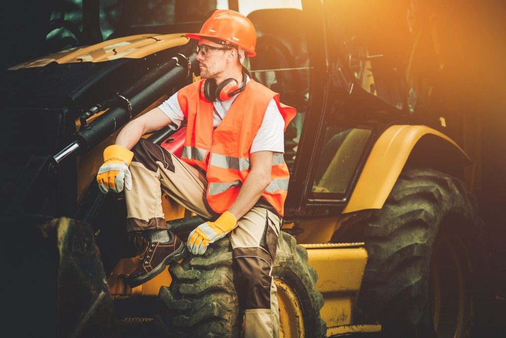 man sitting outside excavator