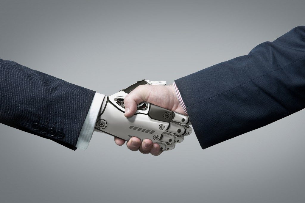 Business human and robot in handshake