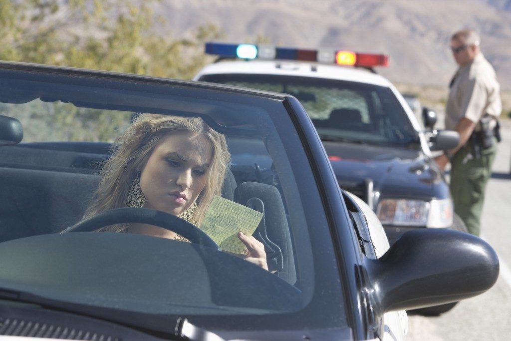 driving girl got a speeding icket from a policeman