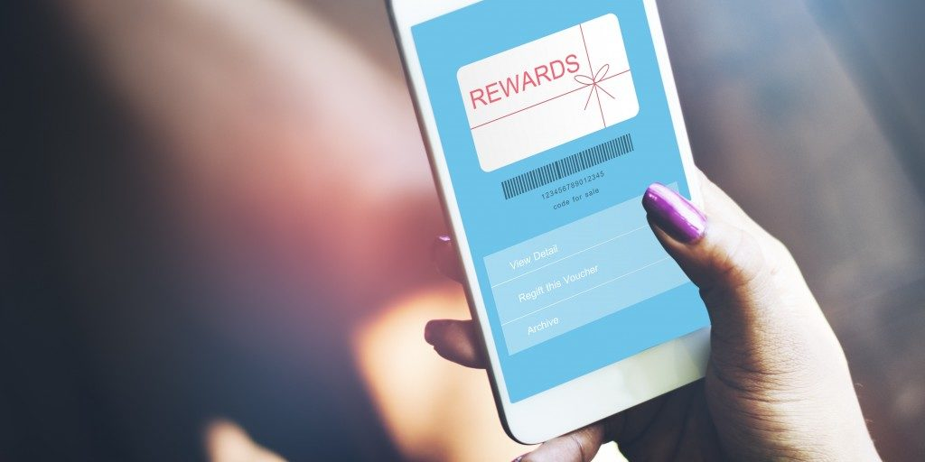woman holding her phone with rewards on screen