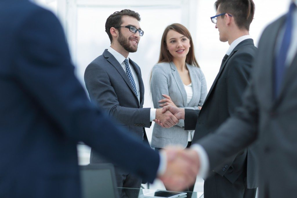 People shaking hands sign of closing deals in the realm of blockchains