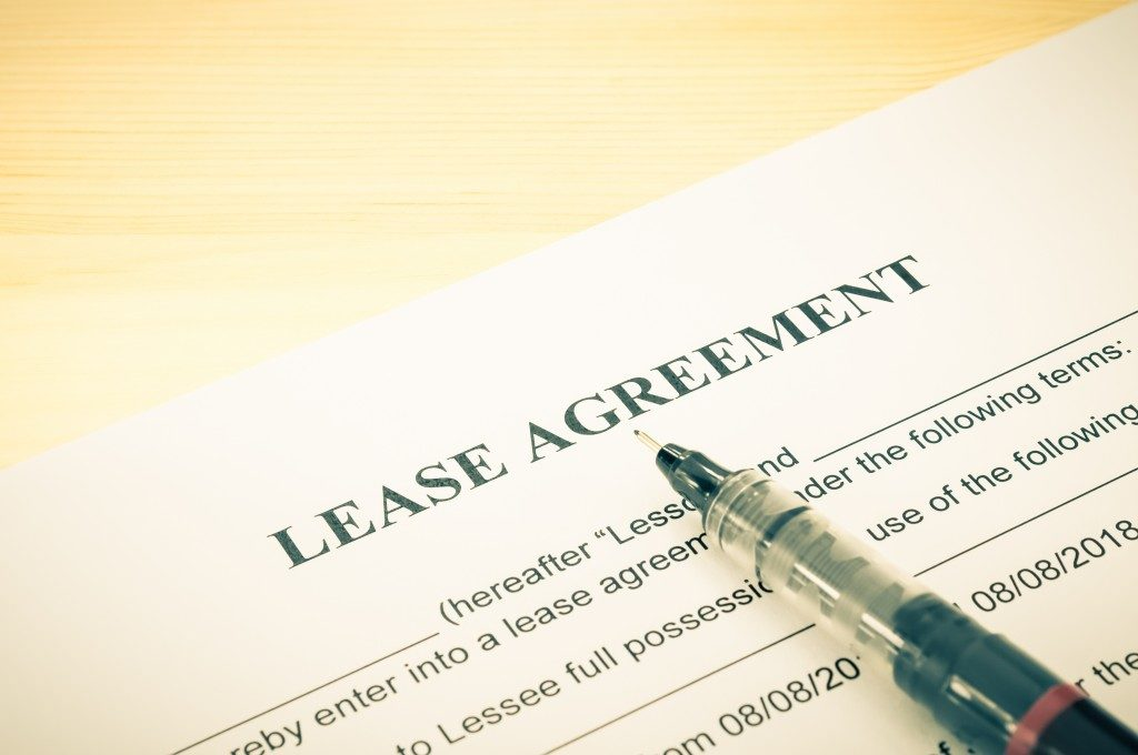 Lease agreement contract sheet and brown pen at bottom right corner on wood table background in vintage style