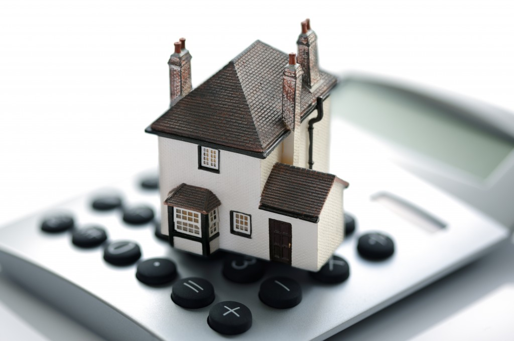 mortgage and house cost concept with model house on top of calculator