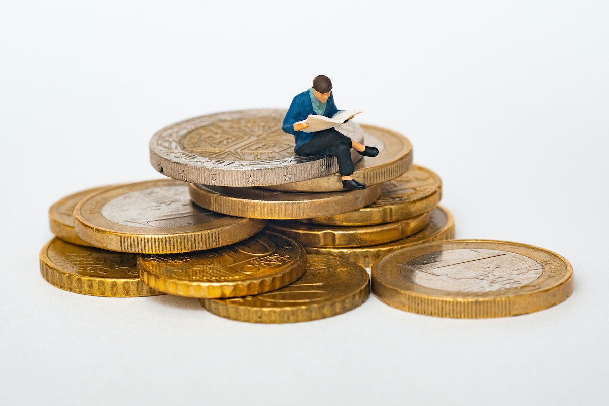 small figure sitting on a pile of coins