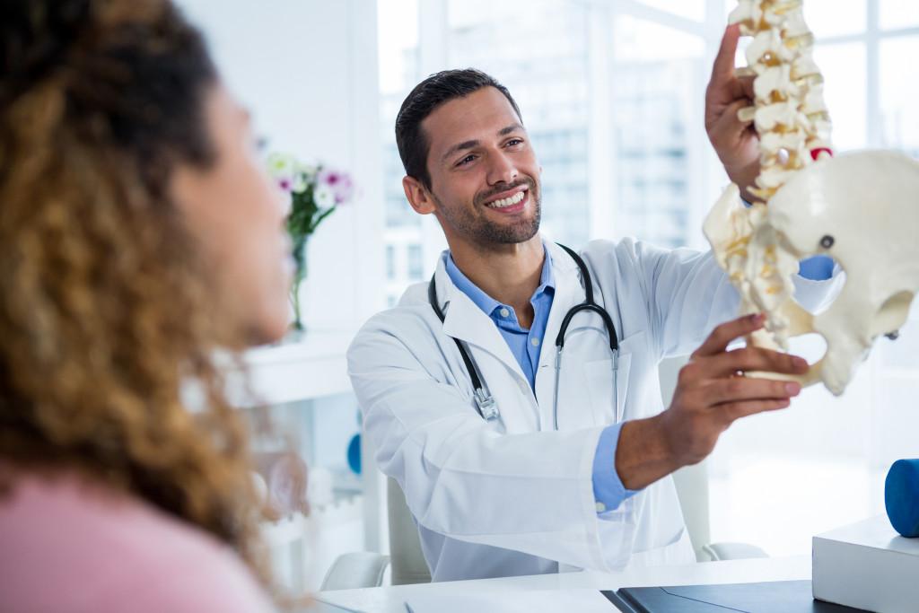 doctor holding skeletal diagram
