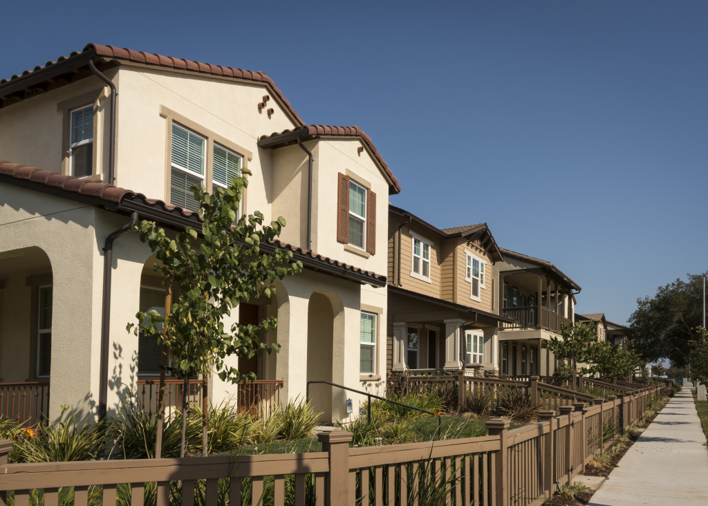 A row of new homes with fenced yards along a sidewalk.